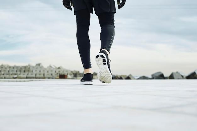 Pés do homem corredor correndo na estrada closeup no sapato