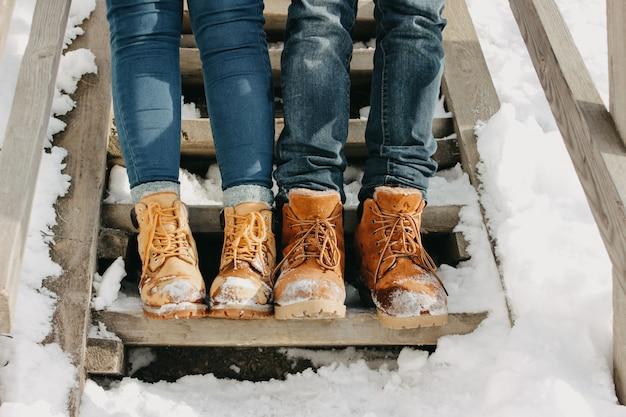 Pés do jovem casal no parque na estação fria.