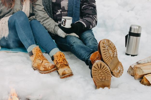 Pés do jovem casal no parque natural da floresta na estação fria.