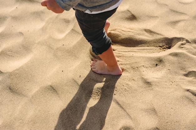 Pés do menino andando na areia da praia.