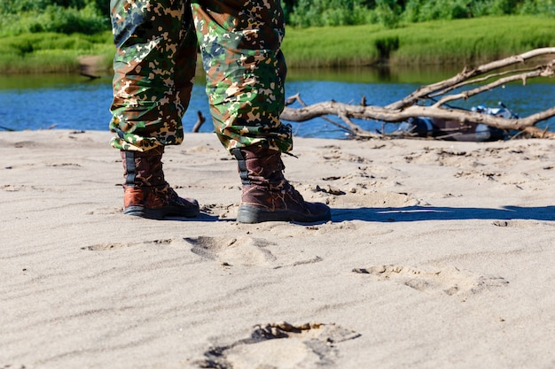Pés dos homens em botas à beira do rio