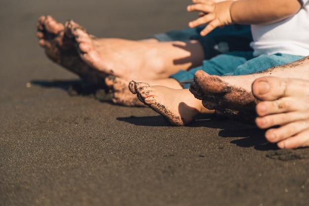 Pés dos pais e do bebê sentado na areia da praia
