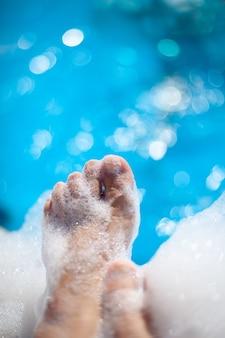 Pés e dedos femininos em espuma em uma festa de relaxamento de espuma na piscina e spa nas férias de verão