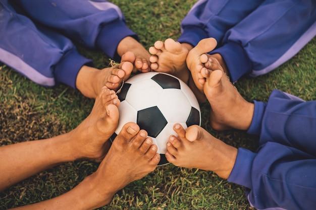 Pés e imagens de conceito de bola de futebol do esporte de trabalho em equipe de crianças