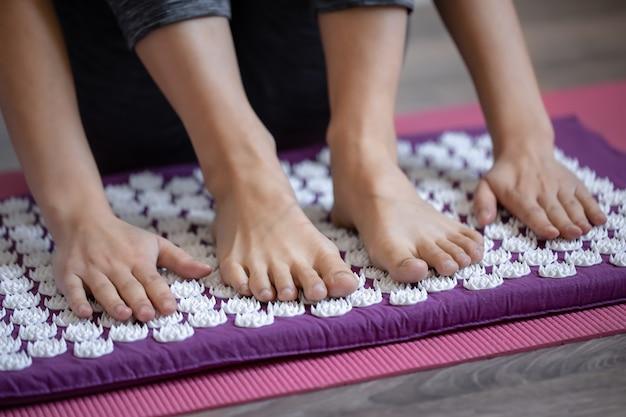 Pés e mãos femininos em almofada e tapete de massagem de acupuntura
