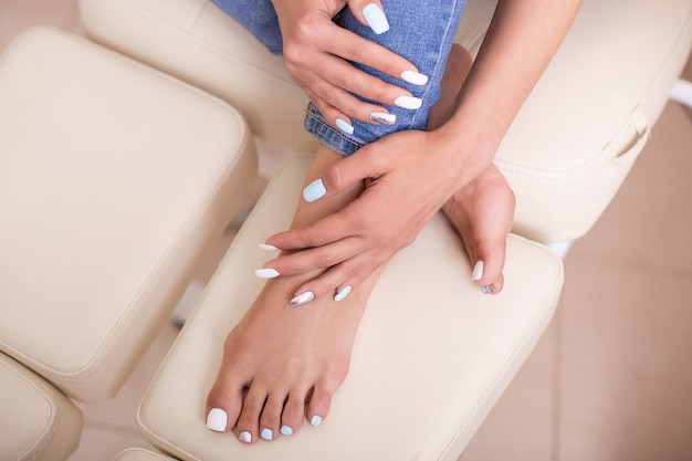 Pés e mãos femininos lindos com unhas elegantes de manicure e pedicure
