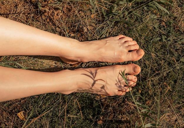 Pés e pernas femininos na grama na vista superior do verão ensolarado