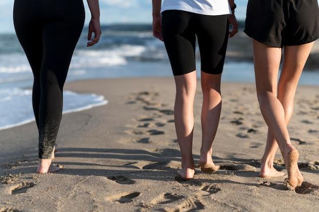 Pés em close caminhando na praia