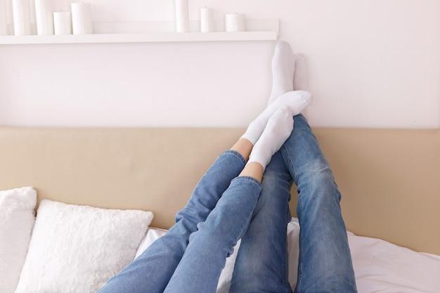 Pés em meias brancas na cama da casa