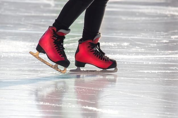 Pés em patins vermelhos na pista de gelo.