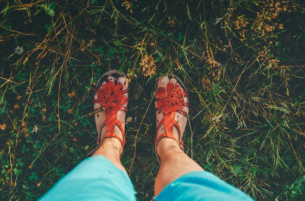 Pés em sandálias na grama verde