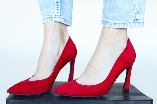 Pés em sapatos de salto vermelho sobre fundo branco