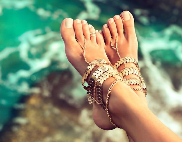 Pés esguios de mulher bronzeada e bem cuidada com pedicure branca elegante vestida com pulseiras de perna dourada no estilo boho acima da água verde do mar tropical partes do corpo cuidados com os pés e pedicure