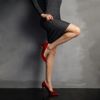 Pés fêmeas desencapados bonitos em sapatas de couro envernizado vermelhas, joelho curvado, vista no perfil.