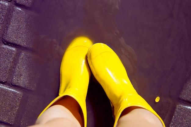Pés fêmeas em botas de borracha amarelas brilhantes na chuva do verão.