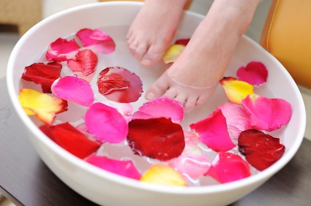 Pés fêmeas no pedicure das pétalas cor-de-rosa. procedimento de spa