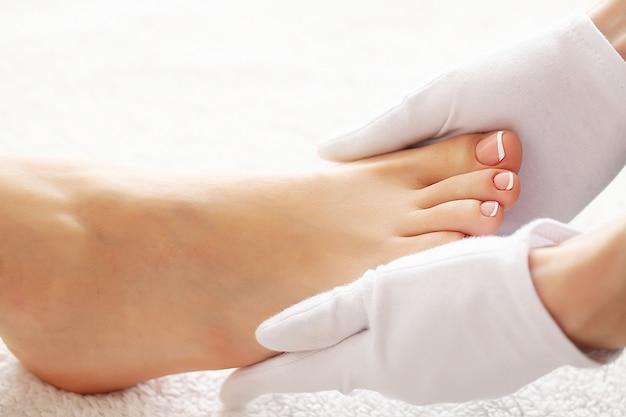 Pés femininos bem cuidados em procedimento de pedicure spa