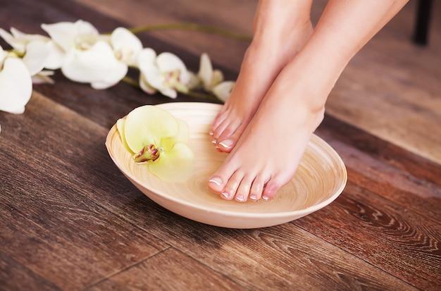 Pés femininos bem cuidados em tigela de madeira de spa com flores e água closeup