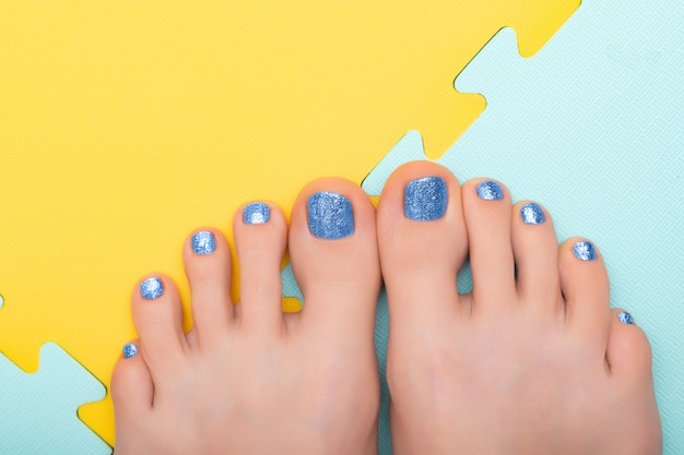Pés femininos bonitos com pedicure glitter azul