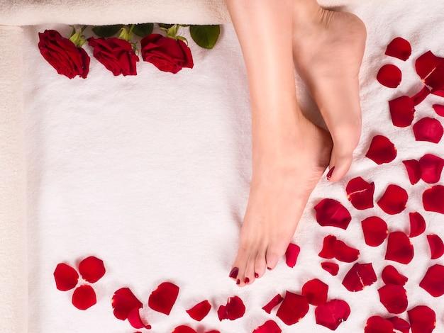 Pés femininos bonitos com uma pedicure bonita em uma toalha de terry com pétalas de rosa. conceito de cuidados de spa e pele.