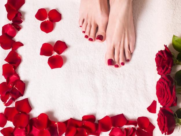 Pés femininos bonitos com uma pedicure vermelha em uma banheira com sal e pétalas de rosa. conceito de cuidados de spa e pele.