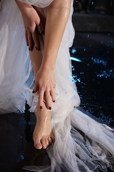 Pés femininos bonitos na água com salpicos. foto em uma luz de néon no estúdio. véu branco ou vestido longo