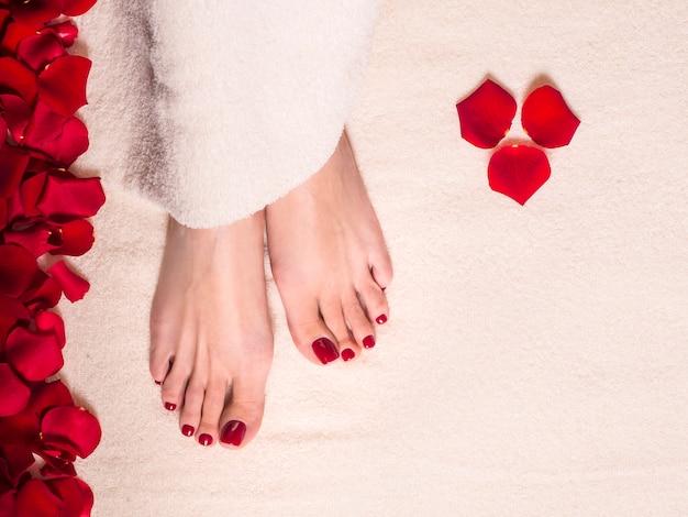 Pés femininos bonitos na toalha de terry com pétalas de rosa. frasco e tubo de creme para cuidados com a pele. spa e conceito de cuidados com a pele