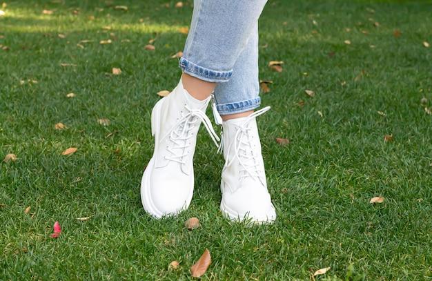 Pés femininos com botas casuais brancas da moda na grama verde com fundo amarelo de folhas de outono