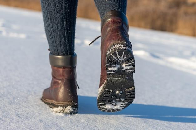 Pés femininos com botas indo embora na neve fresca no inverno. closeup de sapatos de inverno.