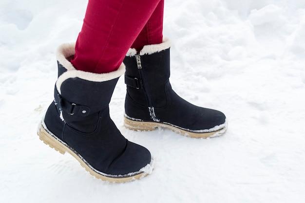Pés femininos com botas pretas caminhando na neve do inverno