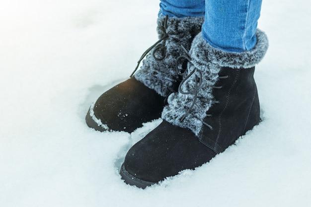 Pés femininos com botas quentes na neve profunda. sapatos de inverno femininos bonitos e práticos.