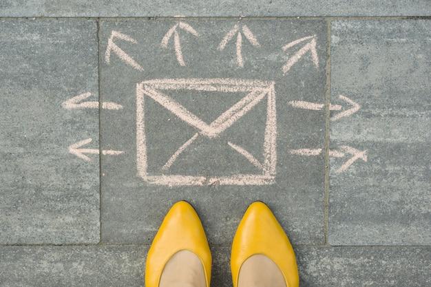 Pés femininos com carta de mensagem envelope abstrata com setas