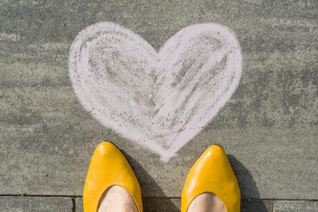 Pés femininos com coração símbolo pintado no asfalto.