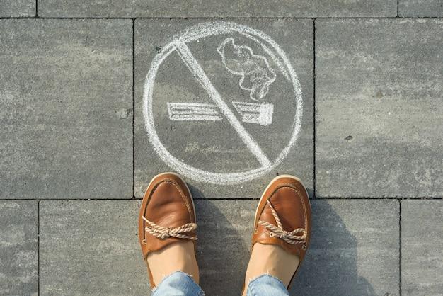 Pés femininos com foto não fumar pintado na calçada cinza