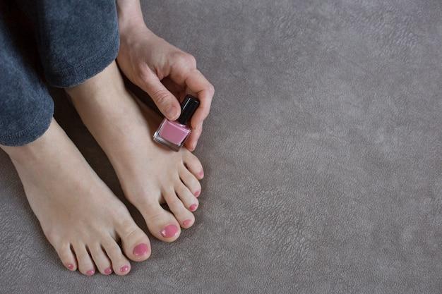 Pés femininos com pedicure rosa