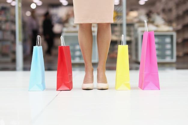 Pés femininos com sapatos ao lado de sacolas de papel multicoloridas no shopping