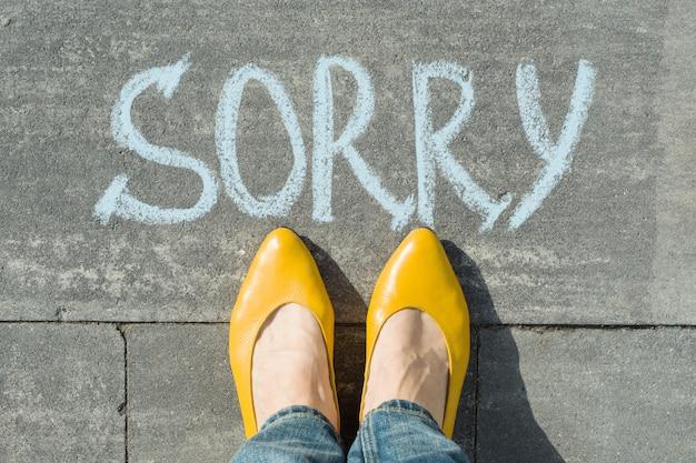 Pés femininos com texto desculpe escrito no asfalto