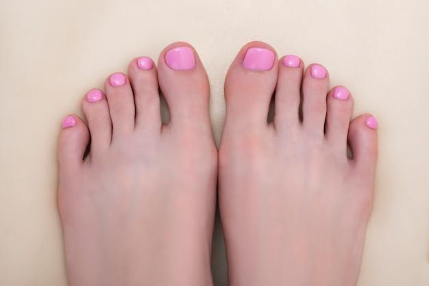 Pés femininos com uma pedicure rosa