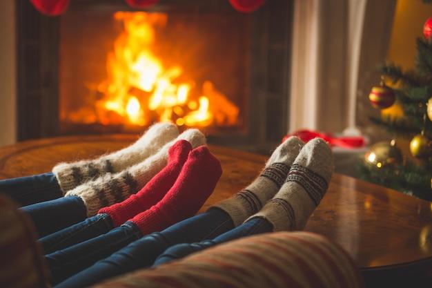 Pés femininos e masculinos em meias de lã aquecendo na lareira do chalé