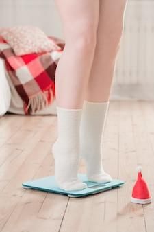 Pés femininos em balanças eletrônicas azuis para controle de peso com chapéu de papai noel de natal no chão de madeira