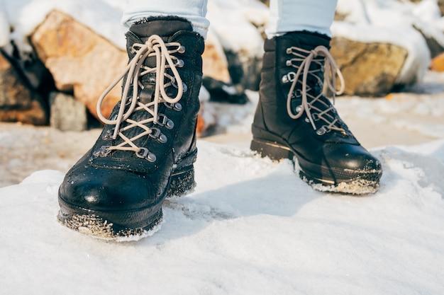 Pés femininos em botas de inverno altas em pé na neve