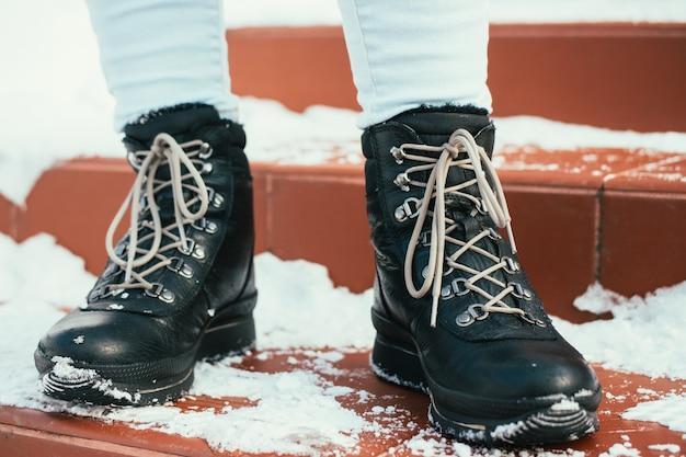 Pés femininos em botas de inverno com atacadores estão nas escadas na neve