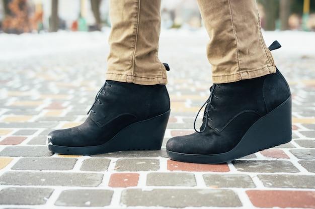 Pés femininos em botas pretas em pé na calçada no inverno, close-up