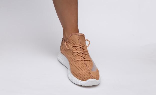 Pés femininos em calçados esportivos da moda em fundo branco