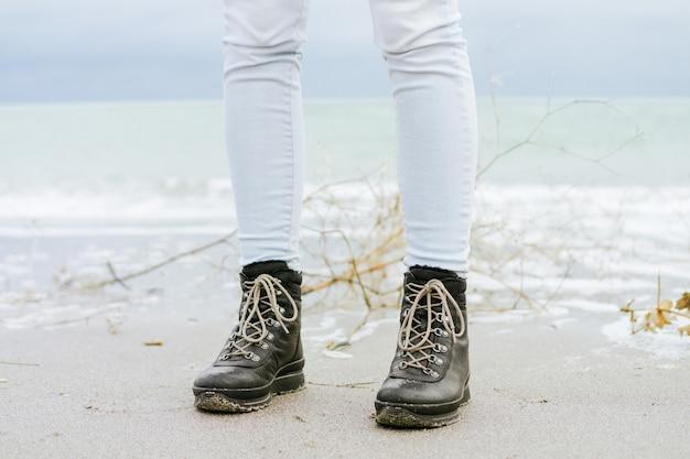 Pés femininos em jeans azul e botas de inverno preto em pé na areia contra o mar