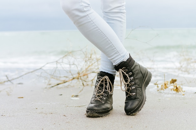 Pés femininos em jeans azul e botas de inverno preto em pé na areia na praia
