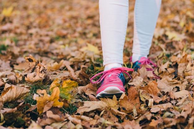 Pés femininos em jeans e tênis rosa andando sobre folhas caídas de outono