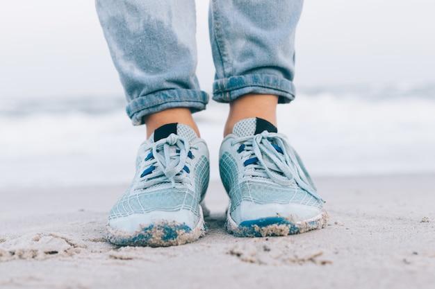 Pés femininos em jeans molhados e tênis