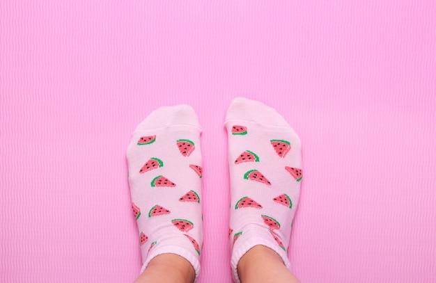 Pés femininos em meias coloridas em melancia impressão sobre um fundo rosa pastel. vista superior. copie o espaço.