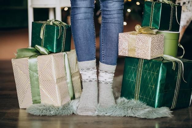 Pés femininos em meias com presente de natal ao redor